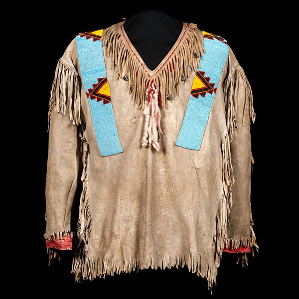 Assiniboine Beaded Hide War Shirt, thread-sewn and beaded using colors of light blue, yellow, red, and black; fringe decorates side seems, neck, and cuffs; Canadian nickels decorate neckline, length 25.5 in. x chest 38 in. early 20th century