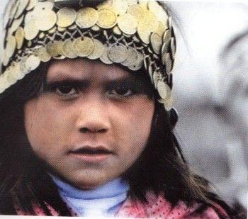 Μικρή Αραουκανή φοράει τα χαρακτηριστικά ελληνικά κρεμαστά φλουρια στο κεφάλι ΠΥΓΜΗ.gr
