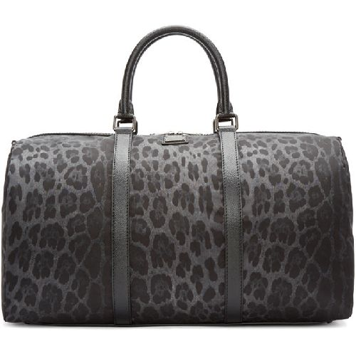 Lightly structured nylon duffle bag featuring leopard pattern in tones of grey throughout. Grained leather trim throughout. Twin carry handles at top. Detachable and adjustable shoulder strap with shoulder pad and lanyard clasp fastening. Logo plaque at face. Bumper studs at base. Two-way zip closure at main compartment. Zippered pocket at interior. Textile lining in black. Gunmetal-tone hardware. Tonal stitching. Approx. 20 length x 13 height x 10 width.
