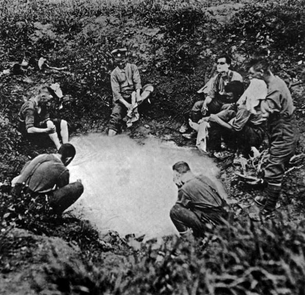 WWI, France; Canadian soldiers of Canadian Expeditionary Force washing and shaving in a water filled shell hole.