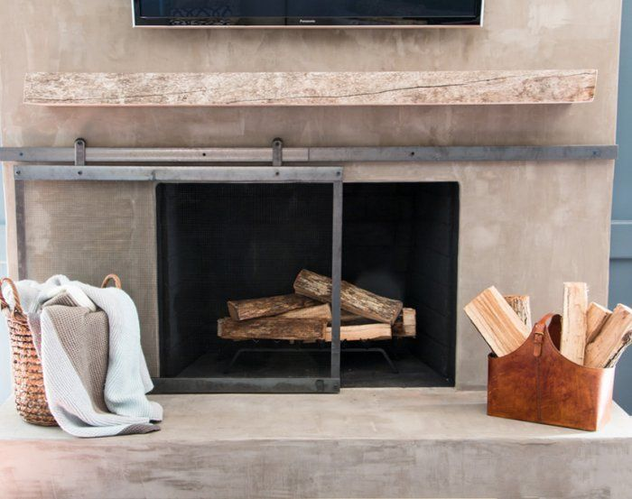 DIY'd sliding fireplace screen (part of an overall fireplace makeover - they DIY'd that concrete overlay as well!