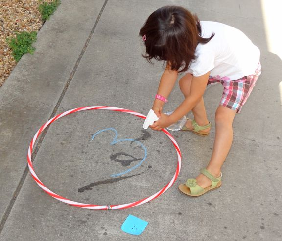 """Children become letter-number detectives.  They """"capture"""" the letter or number on the card they were given by lassoing it with a hula hoop. They make it disappear with a spray bottle. This would be a hoot for children to do at the end of the day.  Teacher could write their names on the sidewalk. :-)"""
