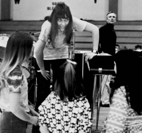 Karen visits with children during a soundcheck as Frank Pooler passes by in background. Long Beach State gymnasium, 1970