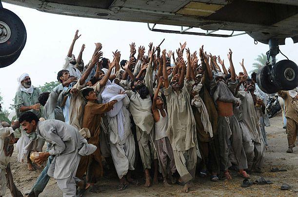 Survivors of the floods in Pakistan reach for food bags dropped by an army helicopter in Lal Pir on August 7.