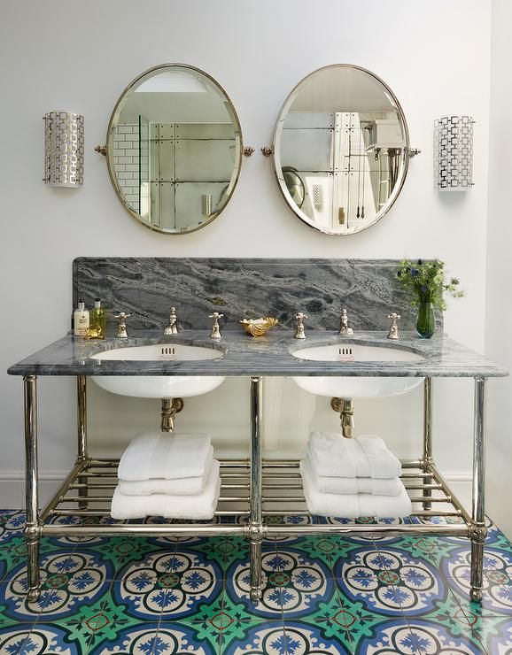Placed on green and blue mosaic floor tiles, a dark gray marble dual washstand is fitted with a towel shelf and sinks paired with polished nickel cross handle faucets mounted in front of a dark gray marble backsplash fixed under two oval pivot mirror lit by Jonathan Adler Parker Wall Sconces.