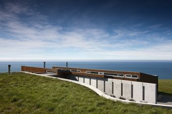 The house is located in a paddock above the sandstone cliffs along the south coast of Dunedin
