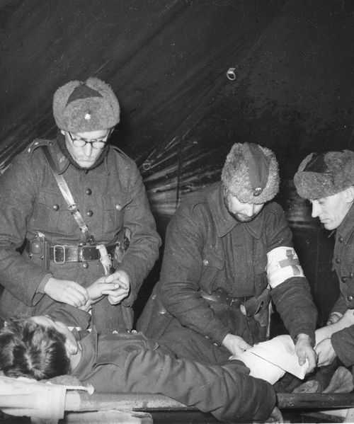 Finnish medics tending to a wounded knee at a field hospital. Winter War