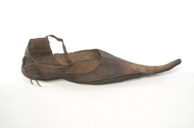 Shoes with long, pointed toes, known as 'poulaines', were fashionable in the late 1300s. Although virtually all shoes at this time were pointed to some degree, it is likely that only the more fashion-conscious members of society wore such extreme examples. The shoe is fastened by a latchet - a leather strap passed through a pair of holes.  Production Date: Late Medieval; late 14th century