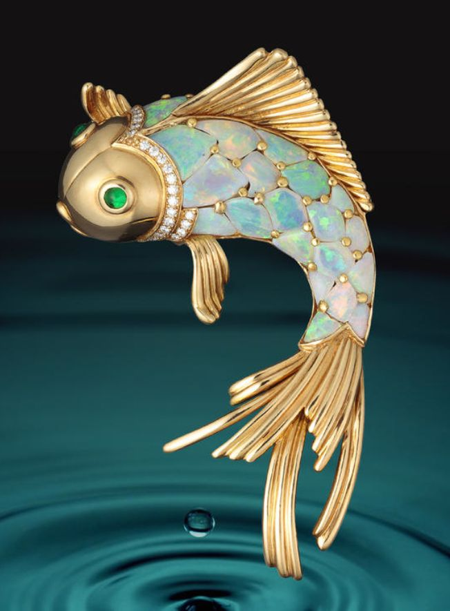 An opal, emerald and diamond brooch, Oscar Heyman & Brothers in the form of a fish, with scales of opals, cabochon emerald eyes and further detailed by round brilliant-cut diamonds; with maker's mark for Oscar Heyman & Brothers, no. 200403; estimated total opal weight: 14.55 carats; mounted in eighteen karat gold; length: 3in. #opals #opalsau #opalsaustralia