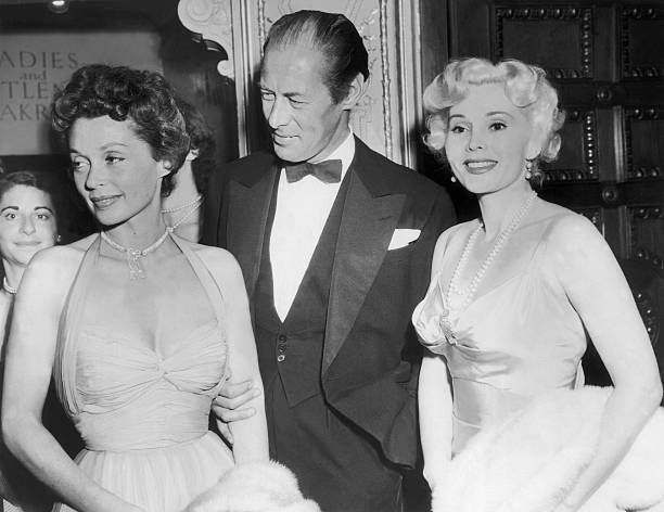 Rex HARRISON arriving at London's Phoenix Theatre for the premiere of the film QUADRILLE, in company of Lilli PALMER (left) and Zsa Zsa GABOR (right).