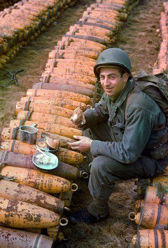 Ingeniero de combate estadounidense come una comida encima de las cajas de municiones almacenadas para la inminente invasión del desembarco de 1944.
