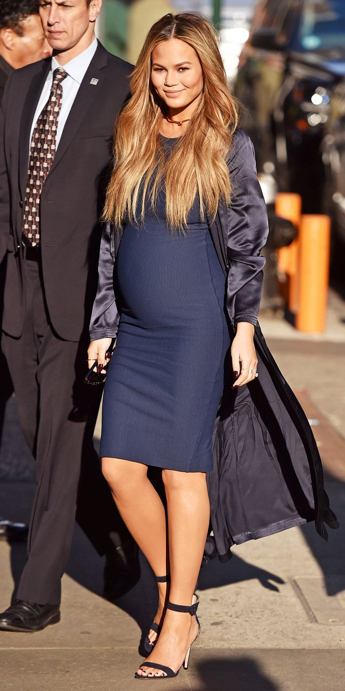 Chrissy Teigen wears a navy blue outfit, which consisted of a curve-hugging dress topped off with a satin duster coat.