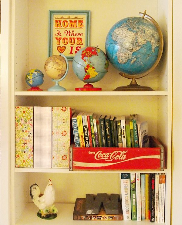 inexpensive white magazine holders  mod podged with scrapbook paper - vintage coke crate holds gardening books - vintage globes - vintage chicken planter
