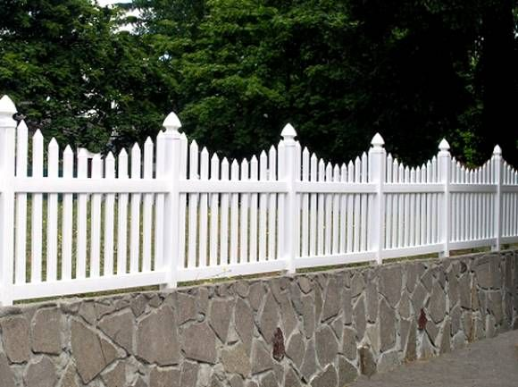 White Picket Fence On Top Of Stone Wall.