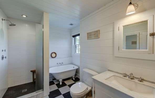 La salle de bain est petite, mais fonctionnelle. Elle compte un bain sur pattes et une douche vitrée... - Zillow/BIG