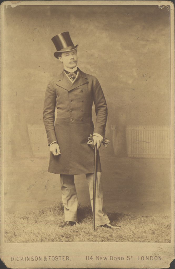 Studio portrait photograph of Colonel Harold, a dapper young gent in a frock coat with silk hat (top hat) and cane, with a backdrop suggesting a fashionable walk in the park. By Dickinson & Foster of London, inscribed on the verso, 1885.