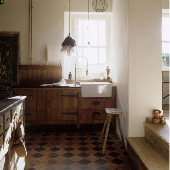 rustic traditional kitchen, reclaimed units and storage, combined with original tiled flooring and a butler's sink, create a warm and intimate rustic feel. white walls brighten the room.