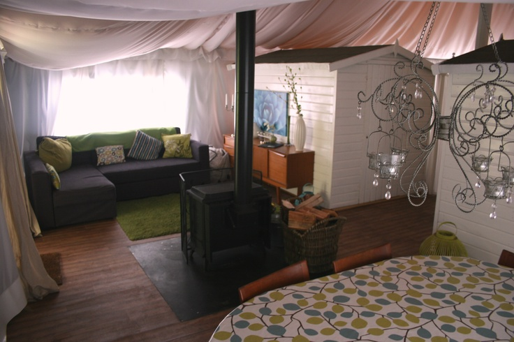inside a deluxe lodge tent! Luxury sofa and woodburning stove