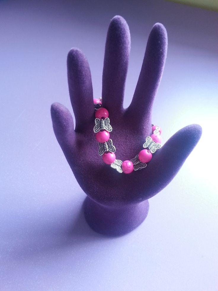 Pulsera de bolas rosas con pequeñas mariposas de plata entre medias. Perfecta para cualquier ocasión.