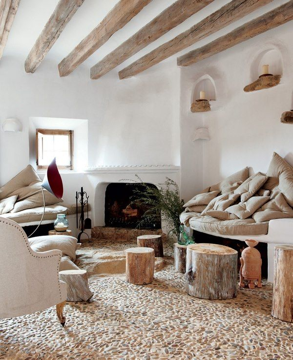 Straw-bale, rustic beams, resident rock, a few logs, a fireplace, lots of cushions and a pebble floor (ouch). Nice space?