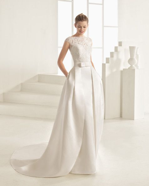 Classic tailored dress and overskirt with beaded lace bodice, mikado skirt and off-the-shoulder sleeves, in natural. Classic tailored dress and overskirt with beaded lace bodice, duchess satin skirt and off-the-shoulder sleeves, in ivory.