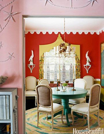 The deep reddish orange of the walls and the turquoise table make bold statements in this dining room in a 1940s Miami bungalow.