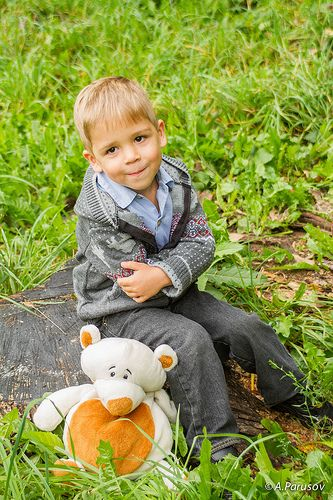 Boy with bear toy on the stump