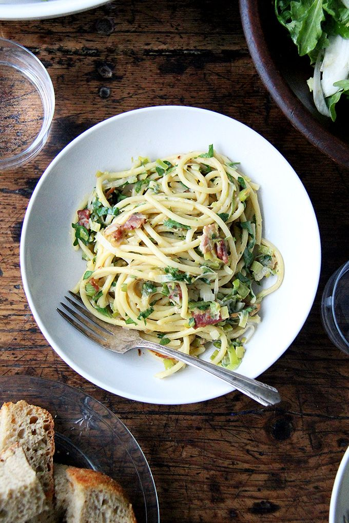 If you're looking for something to make for Valentine's Day, this bucatini carbonara couldn't be simpler to throw together: cook bacon, reserve the fat, use the fat to cook leeks; boil pasta, toss with eggs, fresh lemon juice, grated parmesan, and a little bit of pasta cooking liquid. Toss it all together, add some fresh parsley, and serve with more parmesan and lots of pepper. That's it!