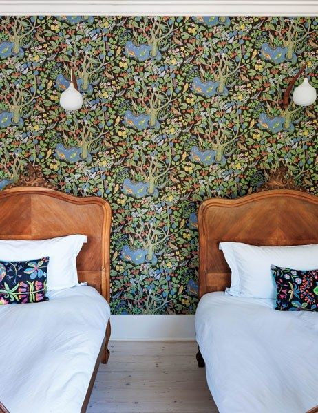 A children's room in London is clad in vibrant Josef Frank wallpaper. The 1960s wall lights were sourced in Stockholm.