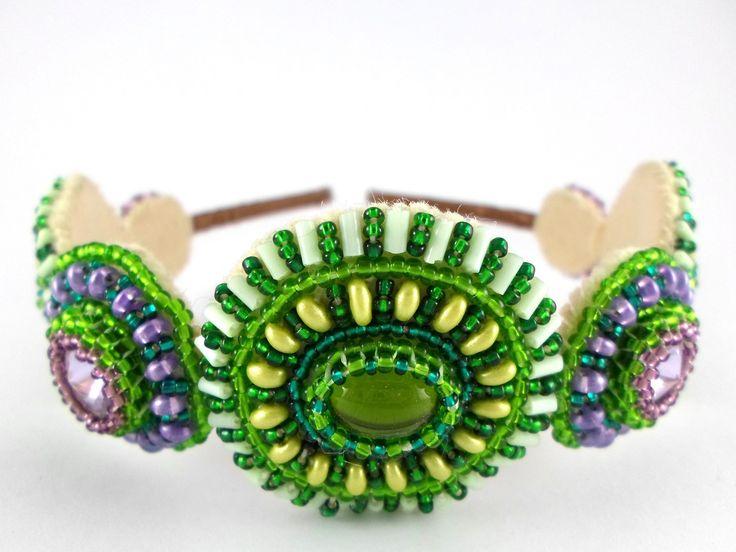 Šeříkové mámení ... čelenka Čelenka Šeříkové mámení patří do kolekce kotoučových čelenek Cercle du Soleil. Středy kruhů tvoří tři zelené skleněné kabošony/mugle a čtyři šeříkové Swarovski rivolky. Čelenka je zpracována metodou korálkové výšivky a peyotovým stehem. Základ čelenky je kovový, umožňuje přizpůsobení velikosti. Čelenka je potažena ...