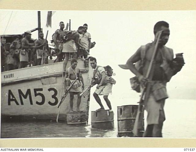 SINGORKAI, NEW GUINEA. 1944-03-19. NATIVE SOLDIERS OF A PLATOON, C COMPANY, PAPUAN INFANTRY BATTALION UNLOADING FROM THE AM53 KAURI WITH A DETACHMENT OF SIGNALS AND CIPHER PERSONNEL