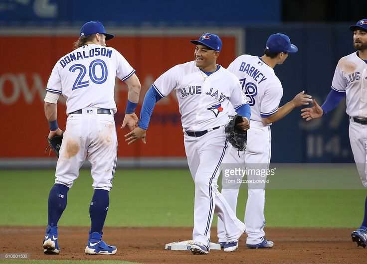 Ezequiel Carrera #3 of the Toronto Blue Jays celebrates their victory with Josh Donaldson #20 during MLB game action against the Baltimore Orioles on September 27, 2016 at Rogers Centre in Toronto, Ontario, Canada.