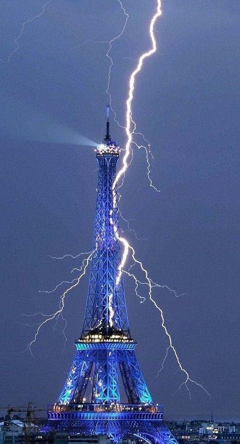 Eiffel tower lights up blue as lightning strikes it...