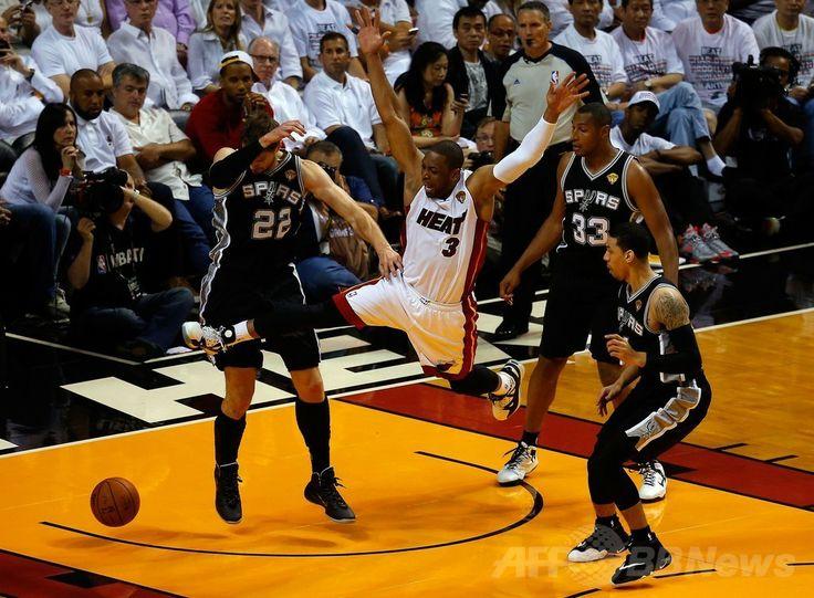 13-14NBAファイナル(7回戦制)、マイアミ・ヒート(Miami Heat)対サンアントニオ・スパーズ(San Antonio Spurs)第3戦。サンアントニオ・スパーズの選手と競り合ってボールを失うマイアミ・ヒートのドウェイン・ウェイド(Dwyane Wade、中央、2014年6月10日撮影)。(c)AFP/Getty Images/Chris Trotman