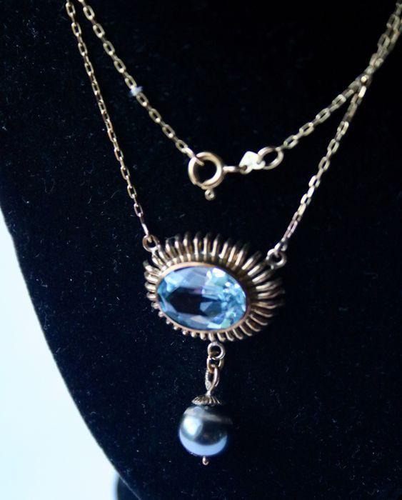 Handgemaakte elegante halsketting in geel goud met een veelzijdige grote blauwe natuurlijke Topas ca. 5 ct VVS1 en echte natuurlijke grijze Tahitian parel ca. 8 9mm. Prachtige staat.  Geel gouden mooie handgemaakte ketting dwarse mid sectie met een veelzijdige natuurlijke blauwe Topas VVS1 ongeveer 153 x 114 mm ca. 50 ct. In de gewilde kleur hemelsblauw omhijnd in soepele frame en omgeven door het uitstralen van decoratieve rand.Movable een echte cultivé grijze Tahitian parel in mooie…