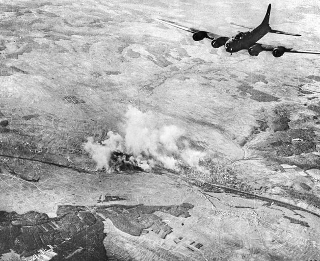 As a B-17 bomber turns toward home, industrial targets in the German city of Schweinfurt billow smoke. An August 1943 Eighth Air Force raid on Schweinfurt cost the Americans 60 Flying Fortresses and their crews. Losses were attributed to both German antiaircraft fire and fighters as the limited range of American Republic P-47 Thunderbolt fighters restricted their ability to escort the B-17s to many targets inside Germany.