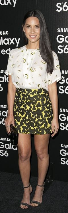 Who made Olivia Munn's yellow print skirt, white short sleeve top, silver sandals, clutch handbag, and jewelry?
