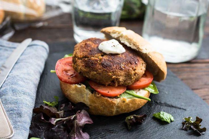 Recept voor tonijnburger voor 4 personen. Met zout, olijfolie, peper, tonijn uit blik, mayonaise, bosui, ciabattabroodje, paneermeel, wit brood, sla en tomaat