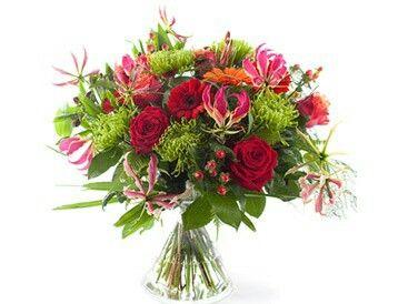 Boeket In de gloria  Feestelijk boeket met vrolijke bloemen zoals chrysant, gerbera, roos, alstroemeria, gloriosa, hypericum, heliconia en natuurlijk groenmateriaal.Verkrijgbaar bij www.bloemenweelde-amsterdam.nl