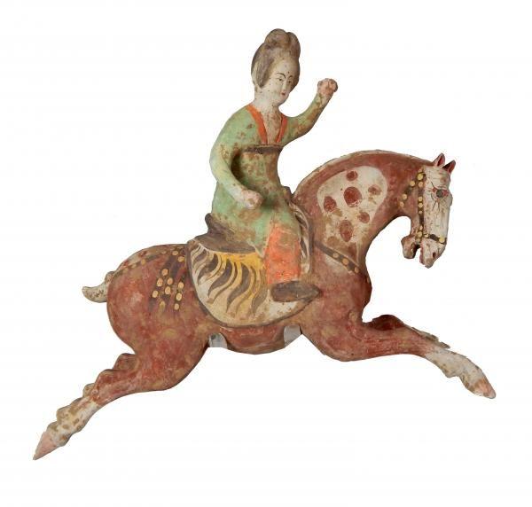 Joueuse de polo sur sa monture saisie dans un «galop volant». La cavalière porte un «hufu», tenue qui se compose d'une tunique, d'un pantalon et de bottes. Les cheveux sont remontés en un chignon stylisé. Tout en bridant son cheval de la main gauche, elle est libre de la droite et peut frapper la balle. En terre cuite à engobe et à polychromie. Chine, époque Tang (618- 907).  H : 27,5 ; L : 33 cm