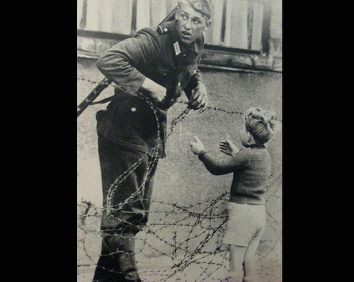 На фото запечатлен караульный, охраняющий периметр, и также маленький мальчик, который пытается попасть в западную часть Берлина к родителям. На фото видно, с какой опаской оглядывается солдат, но он всё же помог малышу перебраться через границу. К сожалению, из-за опубликованного в прессе фото солдата отстранили от несения службы и неизвестно, что с ним случилось дальше.  Источник: