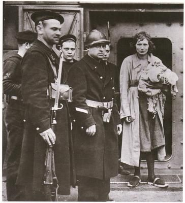 June 17, 1940 : Five minutes before she was shot, this Belgian girl convicted of Fifth Column treason meets her executioners, a firing squad of French marines headed by a corporal in helmet. She is standing in the steel doorway of the Dunkerque fort in which she has just been tried and found guilty. Notice that she wears peasant clogs and carries an armload of belongings. This was part of her disguise as a panic stricken Belgian refugee.