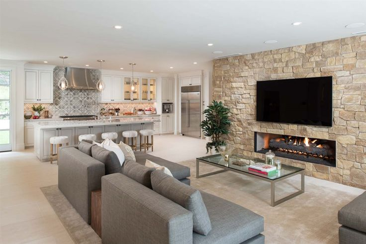 Open kitchen with adjoining living room. Love the stone wall with mounted TV and built-in fireplace.