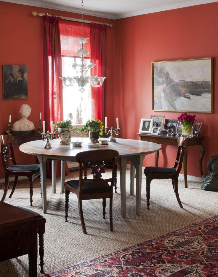 Intensivt röda väggar – och dito gardinlängder – värmer i matrummet.