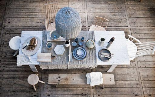 Een witte strandhuistafel, een kleed van ongebleekt linnen, houten zitmeubels en een rieten lamp: puurder kan het niet.