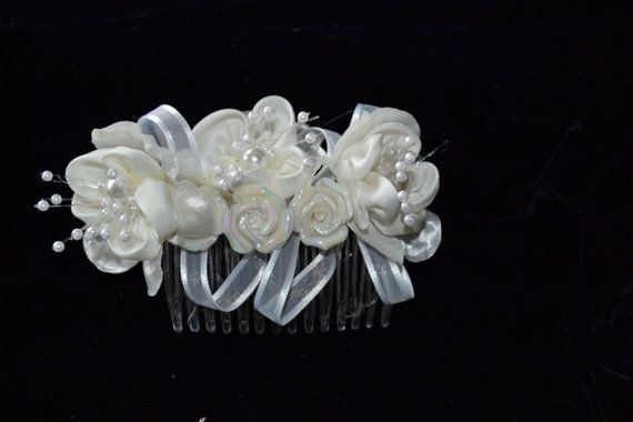Very beautiful comb made of three silk flowers with centres of pearls. white ribbon interlaced between flowers. Accented by three pearlized ceramic