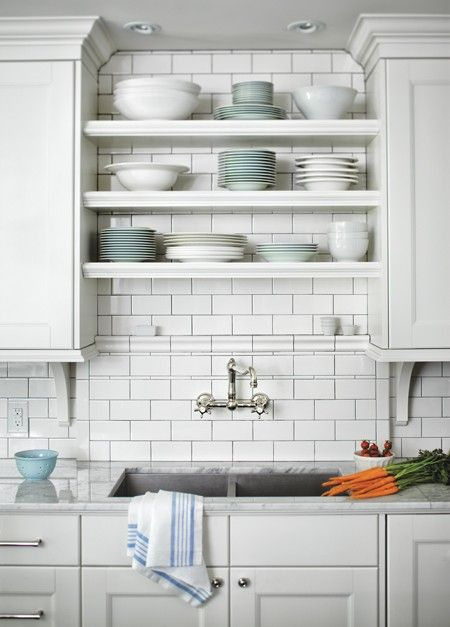 undermount sink with antique faucet. subway tile backsplash. open shelves between cabinets.