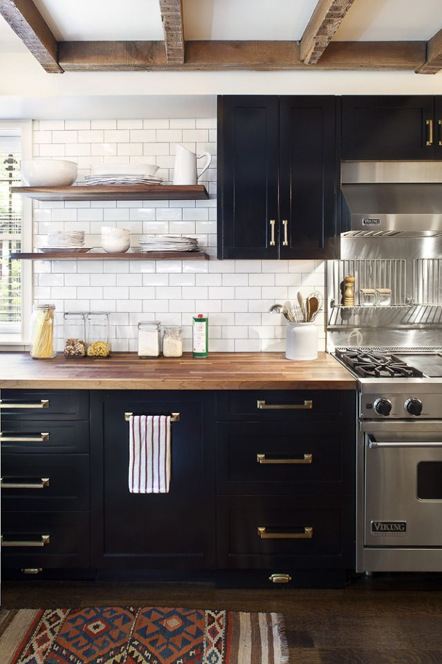 Custom black cabinets with brass hardware and a butcher's block countertop are offset nicely by harder elements like the stainless steel stove.