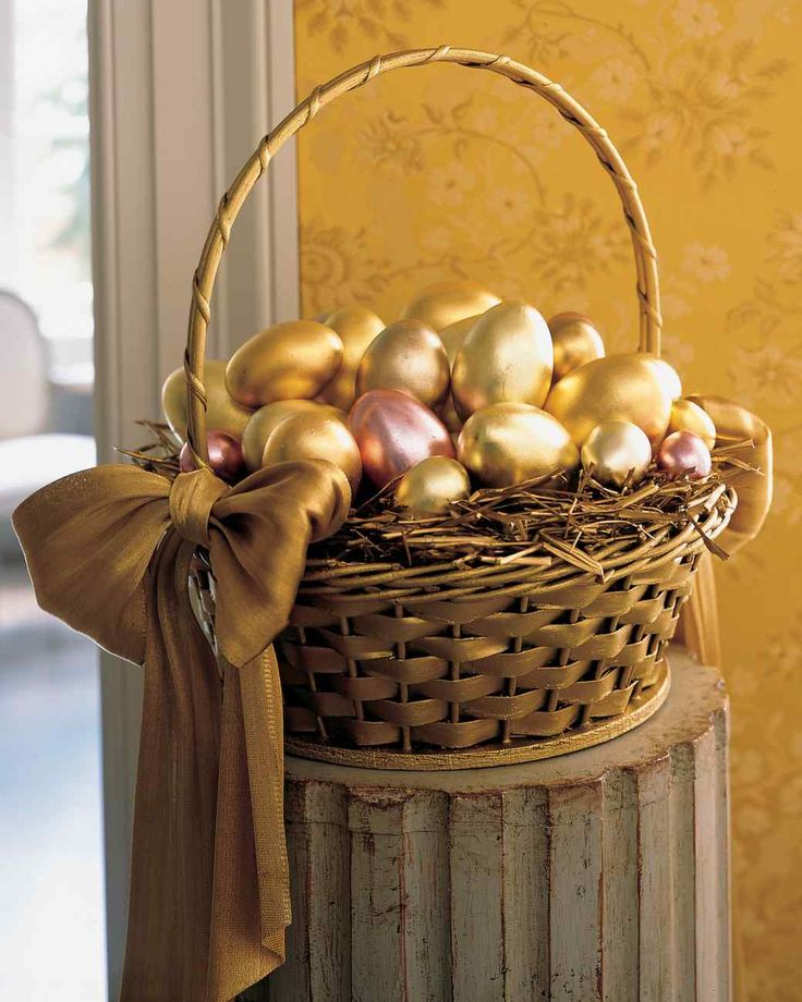 Easter Basket Ideas | Martha Stewart - Create an Easter basket display that resembles a pot of gold at the end of the rainbow. Metallic eggs, covered in varying shades of gold leaf sheets, were set atop a bed of spray-painted hay in a sponge-painted basket. For an elegant finishing touch, tie metallic vintage-ribbon bows on either side of the basket.