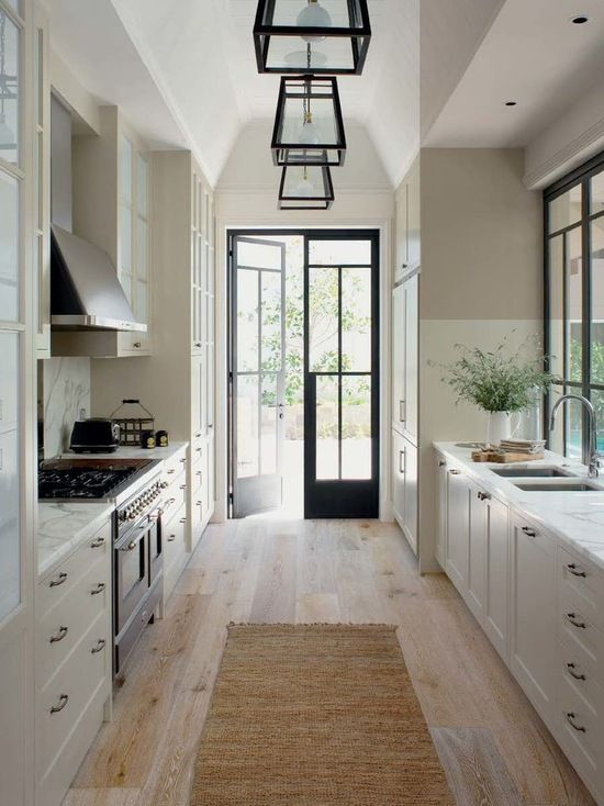 Design ideas for a traditional galley kitchen in Central Coast with a double-bowl sink, shaker cabinets, white cabinets, marble countertops, white backsplash, paneled appliances and light hardwood floors. — Houzz